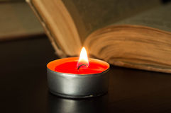The burning candle near the open old book Royalty Free Stock Photo