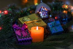 Burning candle and New Year`s gifts royalty free stock images