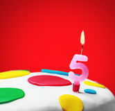 Burning candle with the number five on a birthday cake Royalty Free Stock Photography