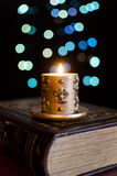 Burning candle and old book Royalty Free Stock Images