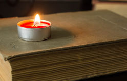 The burning candle on the old book Stock Images