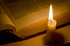Candle and Open Book. Burning candle and old book in the dark Royalty Free Stock Image
