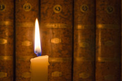 Candle and Books. Burning candle and old books in the dark Stock Image