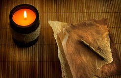 Burning candle with old papers Stock Images