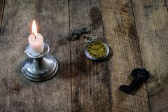 Burning candle and old watch on a wooden table. Flowing time and Royalty Free Stock Images