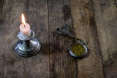 Burning candle and old watch on a wooden table. Flowing time and Royalty Free Stock Photo
