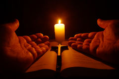 Burning candle, open Bible and prayer hands Stock Photography