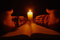 Burning candle, open Bible and prayer hands Stock Photo