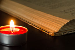 The burning candle and the open old book Royalty Free Stock Image