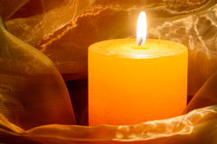Burning candle. Orange burning candle decorated with transparent textile Stock Images