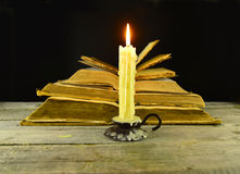 Burning candle with pile of books. Still life with burning candle and pile of shabby old books on black Royalty Free Stock Images