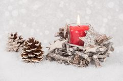 Burning candle and pine cone in the snow Royalty Free Stock Photography