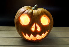 Burning candle with pumpkin head for Halloween Royalty Free Stock Images