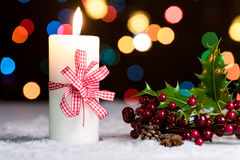 Burning candle with red bow, in snow, with defocussed fairy lights, bokeh Royalty Free Stock Photography