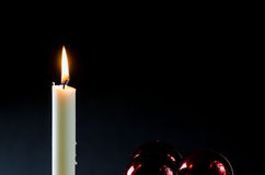 A burning candle with red christmas balls Royalty Free Stock Images