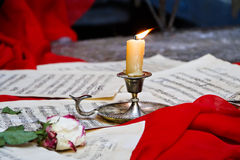 Burning candle on a red cloth, scattered notes. Of withered rose. Love, romance, and music. Inspiration and Memories. Scattered notes. The inspiration of music Royalty Free Stock Photography