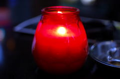 Burning candle in red glass holder and ashtray Stock Images