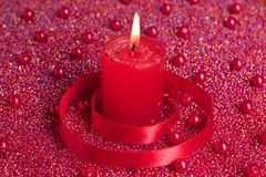 Burning candle with red ribbon Royalty Free Stock Photography