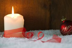 Burning candle with red ribbon. Christmas card. Burning candle with red ribbon and Christmas ball in snow. Christmas card Stock Images