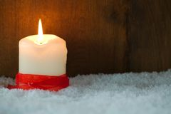 Burning candle with red ribbon. In snow against wooden background Royalty Free Stock Images