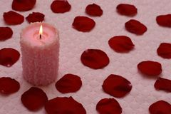 Burning candle and red rose petals. On soft pink textile background with hearts. Valentine`s day concept Royalty Free Stock Image