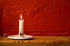 Burning candle red wall Stock Images