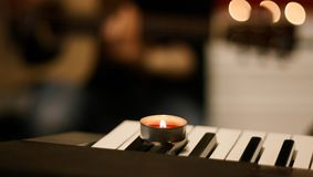 A burning candle with red wax stands on a musical synthesizer stock image