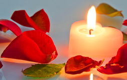 Burning candle in rose petals in heart shape. Burning candle in red rose petals in heart shape Royalty Free Stock Photos