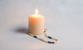 Burning candle and round white pearl beads Royalty Free Stock Photo
