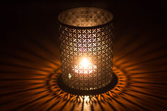 Burning candle in sconce on the table Royalty Free Stock Photography