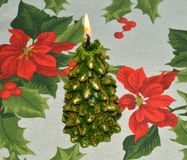 Burning candle in the shape of a Christmas tree on Christmas napkin Royalty Free Stock Photography