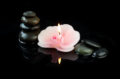 Burning candle in the shape of orchid flower and pebbles on black background Royalty Free Stock Image
