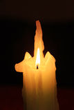 Burning candle with shaped wax Stock Photos