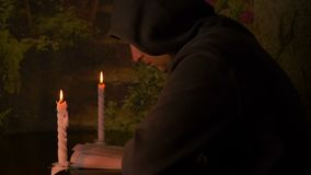 Burning candle in a small white candlestick . A monk in a hood reading a book . Selective focus. Got find evrika stock footage