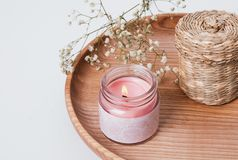 Burning candle and small white flowers on the wooden tray Royalty Free Stock Photos