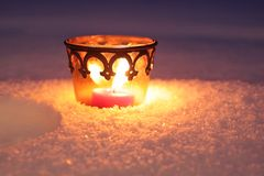 Burning candle in the snow Royalty Free Stock Image