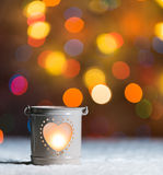 Burning candle, in snow, with defocussed fairy lights, boke in the background, Festive Christmas background Royalty Free Stock Image
