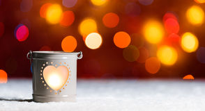 Burning candle, in snow, with defocussed fairy lights, bokeh in the background, Festive Christmas background. Burning candle, in snow, with defocussed fairy Royalty Free Stock Photo