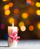 Burning candle, in snow, with defocussed fairy lights, bokeh in the background, Festive Christmas background Royalty Free Stock Images