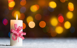 Burning candle, in snow, with defocussed fairy lights, bokeh in the background, Festive Christmas background Royalty Free Stock Image