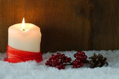 Burning candle in snow Stock Photo