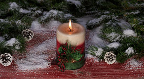 Burning candle on snowy rustic red wooden boards with Christmas Royalty Free Stock Images