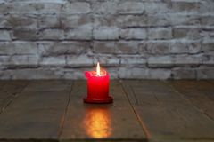 Burning candle standing on a wooden floor stock image