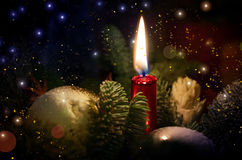 Burning candle stands among the New Year`s toys. Christmas theme. A burning candle stands among the New Year`s toys. Bright particles and bokeh throughout the Stock Images