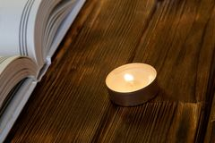 A burning candle stands on wooden planks next to an open white book of both religion and faith stock photos