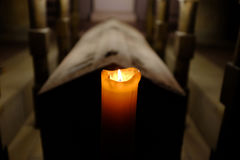 Burning candle with a stone coffin in background. A burning candle in front of a stone coffin royalty free stock image