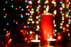 Burning candle on a table with Christmas decorations. On a background garlands Stock Images