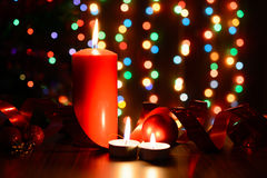 Burning candle on a table with Christmas decorations. On a background garlands Stock Photo