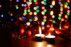 Burning candle on a table with Christmas decorations. On a background garlands Royalty Free Stock Images