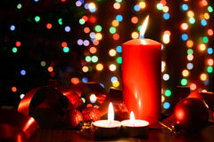 Burning candle on a table with Christmas decorations. On a background garlands Royalty Free Stock Image